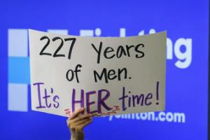 "An sudden remember holds a sign reading ""227 Years of Men.  Its Her Time"" during a ""Get Out to Caucus"" rally with U.S. Democratic presidential candidate Hillary Clinton in Cedar Rapids"